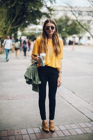 Comment porter: anorak olive, t-shirt à col rond imprimé moutarde, jean skinny noir, bottines chelsea en cuir marron clair
