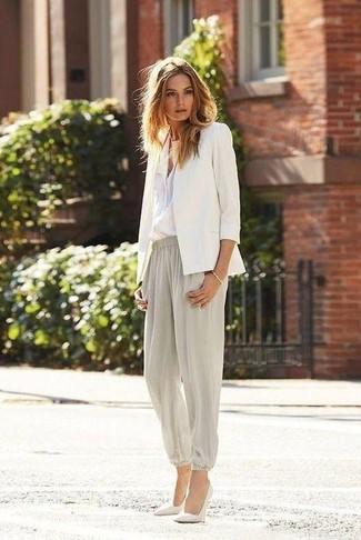 Choisis un blazer blanc et un pantalon carotte gris pour un déjeuner le dimanche entre amies. Termine ce look avec une paire de des escarpins en cuir blancs.
