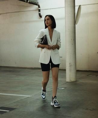 Comment porter un blazer blanc: Harmonise un blazer blanc avec un short cycliste noir pour obtenir un look relax mais stylé. Jouez la carte décontractée pour les chaussures et termine ce look avec une paire de des chaussures de sport noires et blanches.