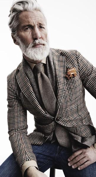 Porte un blazer en pied-de-poule brun et un jean bleu marine pour aller au bureau.