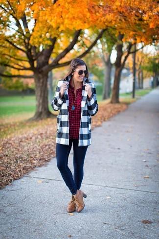 Comment porter un blazer en vichy gris: Pense à harmoniser un blazer en vichy gris avec un jean skinny bleu marine pour achever un style chic et glamour. Cette tenue se complète parfaitement avec une paire de des bottines en cuir marron clair.