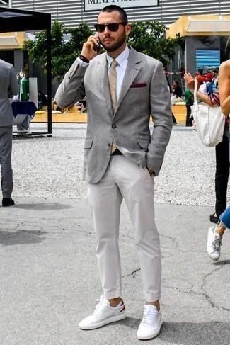 Comment porter une pochette de costume á pois bordeaux: Pense à porter un blazer gris et une pochette de costume á pois bordeaux pour une tenue relax mais stylée. Jouez la carte classique pour les chaussures et complète cet ensemble avec une paire de des baskets basses en toile blanc et rouge.