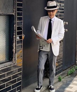 Comment porter une cravate en tricot noire: Essaie de marier un blazer blanc avec une cravate en tricot noire pour une silhouette classique et raffinée. Tu veux y aller doucement avec les chaussures? Fais d'une paire de des baskets basses en toile noires et blanches ton choix de souliers pour la journée.
