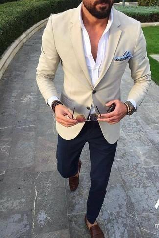 Comment porter un blazer beige: Pense à marier un blazer beige avec un pantalon de costume bleu marine pour dégager classe et sophistication. Complète ce look avec une paire de des slippers en cuir marron foncé.