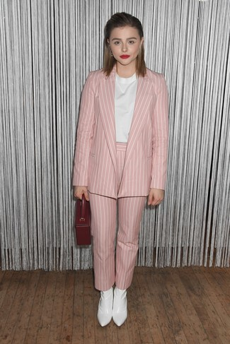 Comment porter: blazer à rayures verticales rose, chemisier à manches courtes blanc, pantalon carotte à rayures verticales rose, bottines en cuir blanches