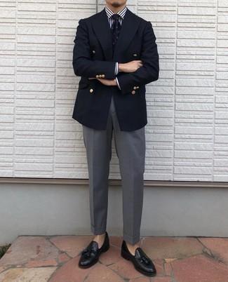 """Tendances mode hommes: L'association d'un blazer croisé bleu marine et d'un pantalon de costume gris te démarquera de la masse sans trop être """"too much"""". Une paire de mocassins à pampilles en cuir noirs apporte une touche de décontraction à l'ensemble."""