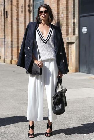 Comment porter des sandales à talons en daim noires: Porte un blazer croisé à rayures verticales noir et une jupe-culotte blanche pour créer un style chic et glamour. Complète ce look avec une paire de des sandales à talons en daim noires.
