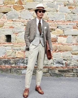 """Comment porter un blazer en vichy noir et blanc: L'association d'un blazer en vichy noir et blanc et d'un pantalon de costume beige te démarquera de la masse sans trop être """"too much"""". Une paire de des chaussures brogues en cuir marron est une option astucieux pour complèter cette tenue."""