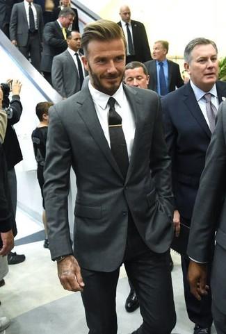Associe un blazer gris foncé avec un pantalon de costume noir pour une silhouette classique et raffinée.