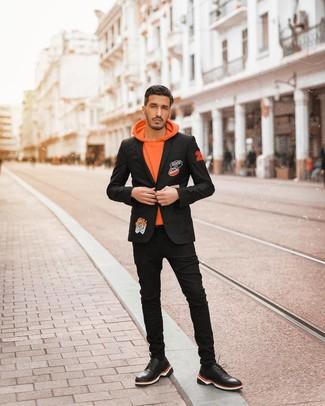 Comment porter: blazer brodé noir, sweat à capuche orange, jean skinny noir, chaussures de sport en cuir noires