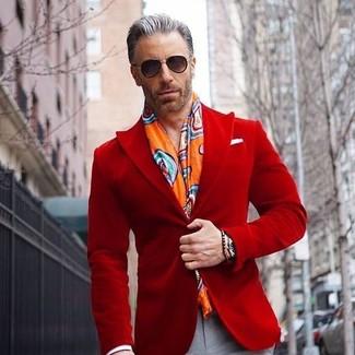 Comment porter: blazer en velours rouge, pantalon de costume gris, écharpe imprimée orange, lunettes de soleil noires