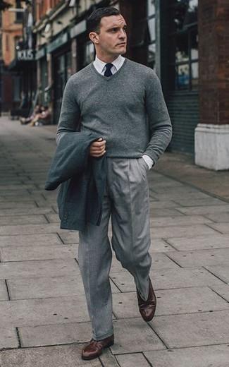Comment porter un pull à col en v gris: Fais l'expérience d'un style classique avec un pull à col en v gris et un pantalon de costume gris. Assortis ce look avec une paire de des chaussures derby en cuir marron foncé.