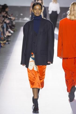 Comment porter: blazer noir, pull à col roulé bleu marine, jupe mi-longue imprimée orange, chaussures richelieu en cuir noires