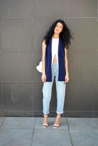 Comment porter: blazer sans manches bleu marine, débardeur blanc, jean boyfriend bleu clair, sandales à talons en cuir blanches