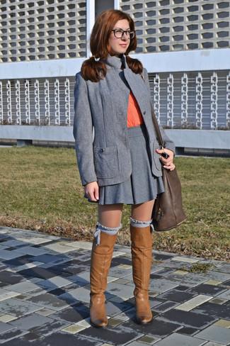 Comment porter: blazer gris, t-shirt à col rond orange, jupe patineuse grise, bottes hauteur genou en cuir marron