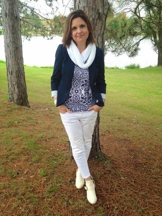 Comment porter: blazer bleu marine, top sans manches imprimé bleu marine et blanc, jean blanc, bottines en cuir beiges