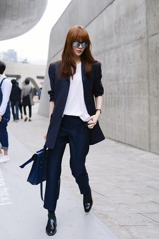 Comment porter: blazer à rayures verticales bleu marine, top sans manches en soie blanc, pantalon de costume à rayures verticales bleu marine, slippers en cuir noirs