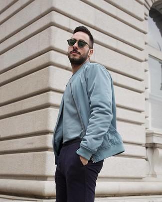 Comment porter: blouson aviateur bleu clair, t-shirt à col rond bleu clair, pantalon chino bleu marine, lunettes de soleil vert foncé