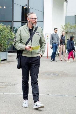 Comment porter une besace en toile noire: Essaie d'associer un blouson aviateur vert menthe avec une besace en toile noire pour un look confortable et décontracté. Termine ce look avec une paire de des chaussures de sport blanches et noires.