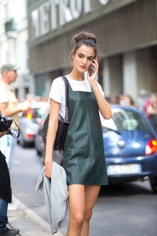 Comment porter: blouson aviateur gris, robe chasuble en cuir vert foncé, t-shirt à col rond blanc, cartable en cuir matelassé noir