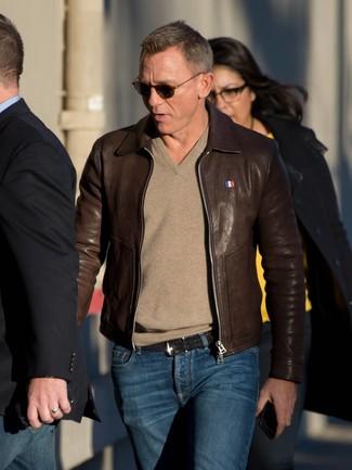 Tenue de Daniel Craig: Blouson aviateur en cuir marron foncé, Pull à col en v marron clair, Jean bleu marine, Ceinture en cuir tressée noire