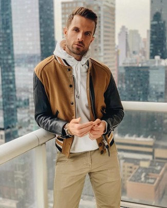 Comment porter: blouson aviateur marron, sweat à capuche blanc, pantalon chino marron clair, montre en cuir marron