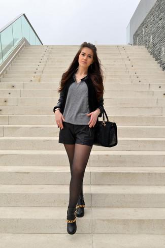 Comment porter: blouson aviateur en cuir noir, pull à col en v gris, short en cuir noir, bottines en cuir ornées noires