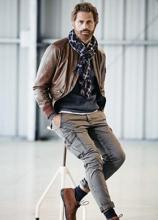 Comment porter: blouson aviateur en cuir marron, pull à col rond bleu marine, pantalon cargo gris, bottines chukka en daim marron