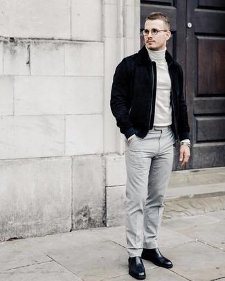 Comment porter: blouson aviateur en daim bleu marine, pull à col roulé blanc, pantalon de costume gris, bottines chelsea en cuir noires