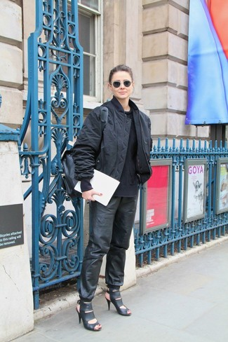 Comment porter: blouson aviateur noir, pull torsadé noir, pantalon de jogging en cuir noir, sandales à talons en cuir noires