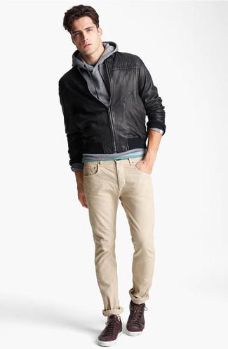 Comment porter: blouson aviateur en cuir noir, sweat à capuche gris, t-shirt à col rond vert, jean beige