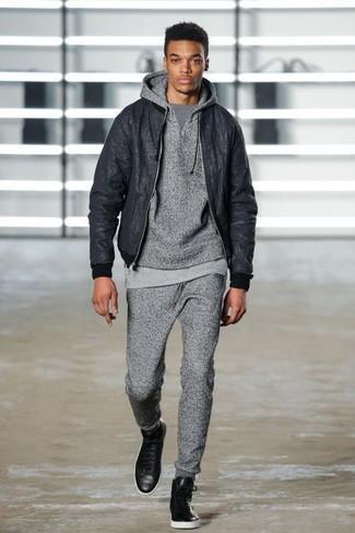 Comment porter: blouson aviateur noir, sweat à capuche gris, t-shirt à col rond gris, pantalon de jogging gris