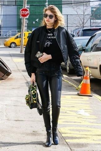 Comment porter: blouson aviateur noir, sweat-shirt imprimé noir et blanc, leggings en cuir noirs, bottines en cuir noires