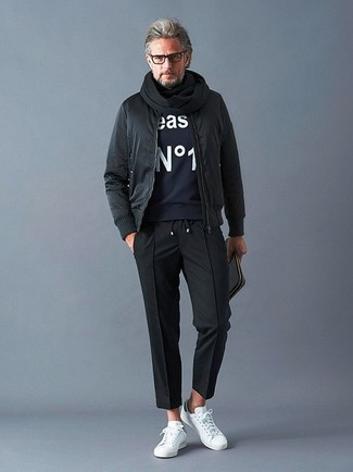 Comment porter: blouson aviateur noir, sweat-shirt imprimé bleu marine, pantalon chino noir, baskets basses en cuir blanches