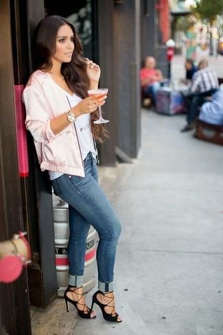 Comment porter: blouson aviateur en satin rose, t-shirt à col en v imprimé blanc, jean skinny bleu, sandales à talons en daim noires