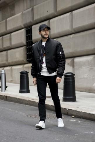 Comment porter: blouson aviateur noir, t-shirt à col rond imprimé blanc, jean noir, baskets basses blanches