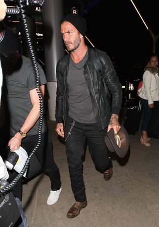 Tenue de David Beckham: Blouson aviateur en cuir noir, T-shirt à col rond gris foncé, Jean noir, Chaussures derby en cuir marron foncé