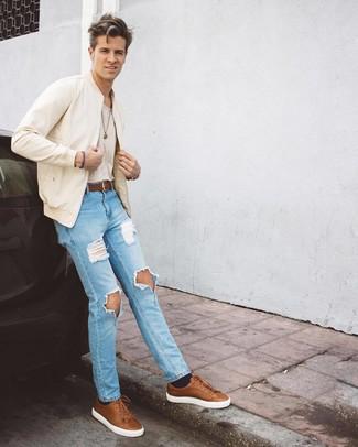 Comment porter: blouson aviateur beige, t-shirt à col rond beige, jean déchiré bleu clair, baskets basses en cuir marron