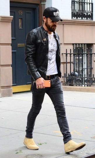 Comment porter: blouson aviateur en cuir noir, t-shirt à col rond imprimé blanc et noir, jean skinny gris foncé, bottines chelsea en daim marron clair