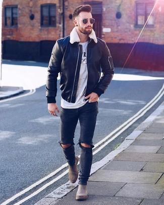 Comment porter: blouson aviateur en cuir noir, t-shirt à col rond imprimé blanc et noir, jean skinny déchiré noir, bottines chelsea en daim grises