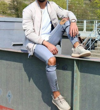 Comment porter: blouson aviateur beige, t-shirt à col rond blanc, jean skinny déchiré bleu clair, chaussures de sport beiges