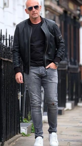 Comment porter: blouson aviateur en cuir noir, t-shirt à col rond noir, jean skinny déchiré gris, baskets basses en cuir blanches
