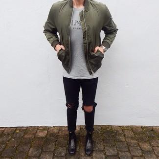 Comment porter: blouson aviateur olive, t-shirt à col rond imprimé gris, jean skinny déchiré noir, bottines chelsea en cuir noires