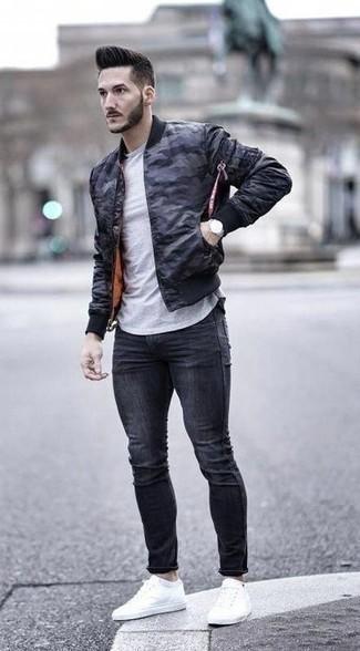 Comment porter un jean skinny gris foncé: Pour une tenue aussi confortable que ton canapé, associe un blouson aviateur camouflage bleu marine avec un jean skinny gris foncé. Une paire de des baskets basses en toile blanches est une façon simple d'améliorer ton look.