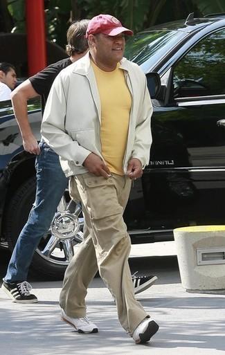 Comment porter: blouson aviateur blanc, t-shirt à col rond jaune, pantalon cargo beige, chaussures de sport blanches