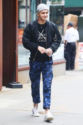 Comment porter: blouson aviateur noir, t-shirt à col rond imprimé noir et blanc, pantalon cargo camouflage bleu, baskets basses en cuir imprimées blanches