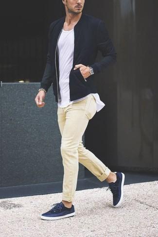 Comment porter: blouson aviateur noir, t-shirt à col rond blanc, pantalon chino jaune, baskets basses bleu marine
