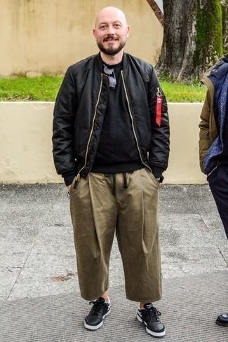 Comment porter un pantalon chino marron clair quand il fait chaud: Ce combo d'un blouson aviateur noir et d'un pantalon chino marron clair te permettra de garder un style propre et simple en dehors des horaires de bureau. Si tu veux éviter un look trop formel, termine ce look avec une paire de des baskets basses en cuir noires.