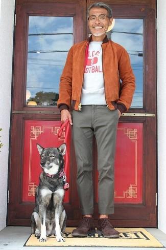 Comment porter: blouson aviateur en daim tabac, t-shirt à col rond imprimé blanc et rouge, pantalon chino gris, bottines chukka en daim bordeaux