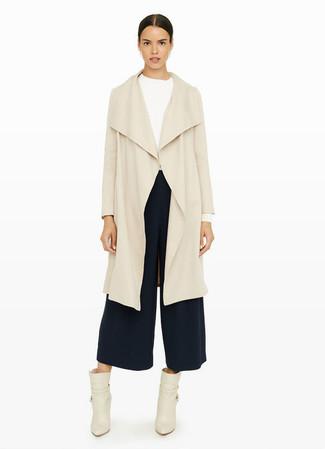 Ce combo d'un cache-poussière beige et d'une jupe-culotte bleue marine dégage une impression très décontractée et accessible. Une paire de des bottines en cuir beiges apportera une esthétique classique à l'ensemble.